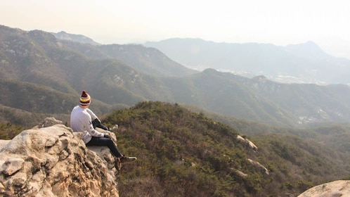 Hiker sitting on mountain peak observing the distance.
