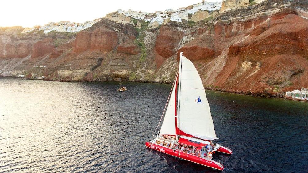 Show item 9 of 9. Catamaran sailing near cliffs in Santorini