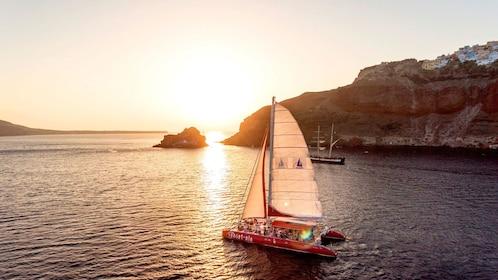 Catamaran sailing while sun sets in Santorini