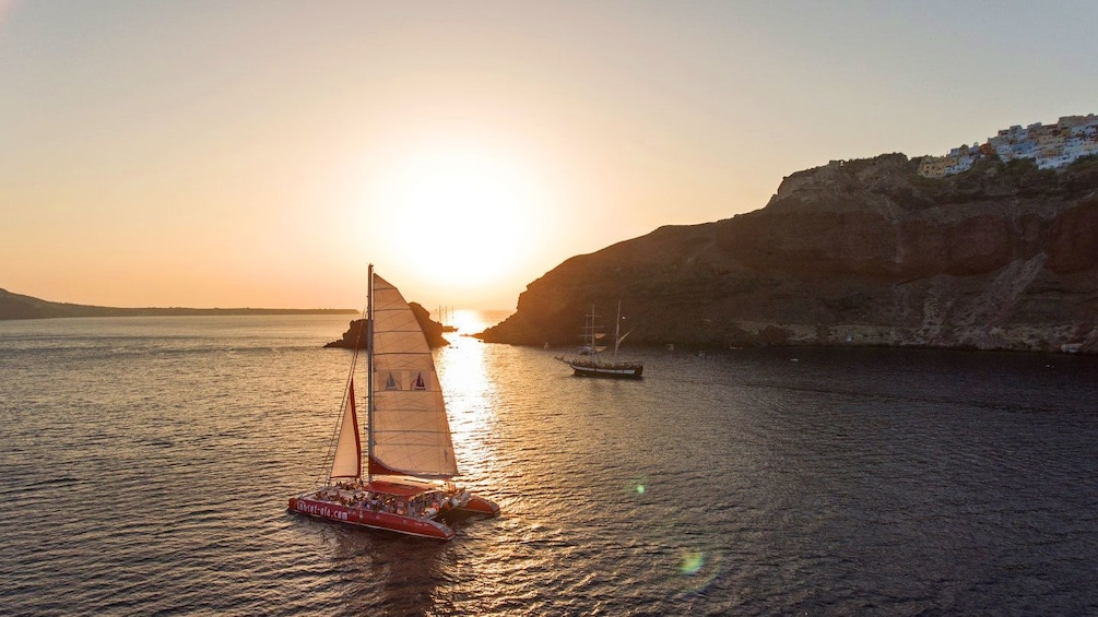 Show item 3 of 9. Catamaran sailing while sun sets in Santorini