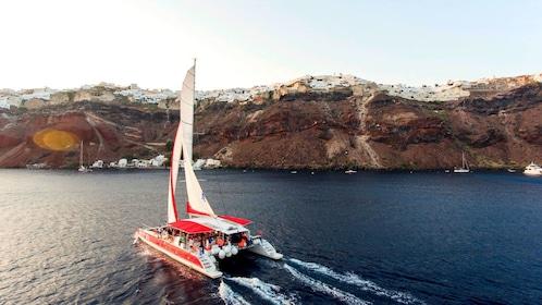 Catamaran sailing near cliffs in Santorini