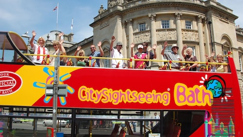 People waving from the top of a Hop-On Hop-Off bus in Bath