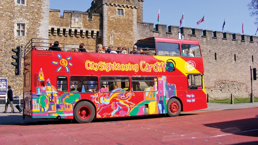Show item 3 of 10. riding a red double decker bus along a historical building in Cardiff