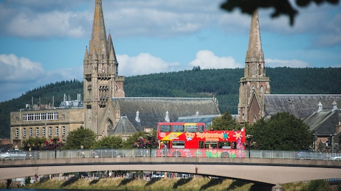 Red tour bus passing over bridge in Inverness.