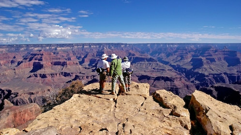 hikers standing on a cliff at Grand Canyon