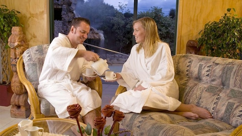 Couple enjoying tea time while wrapped in white robes at the Wai Ora Mud Bath and Spa in Rotorua, New Zealand