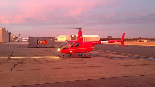 Red helicopter landed in runway at twilight.
