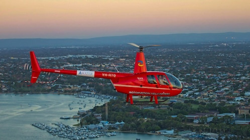 Red helicopter flying over Fremantle at twilight.