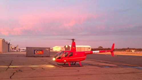 Red helicopter in runway at twilight.