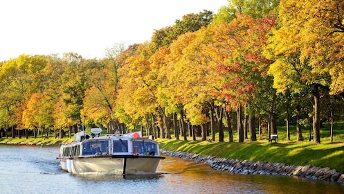 Tour boat passing by colorful trees in Stockholm