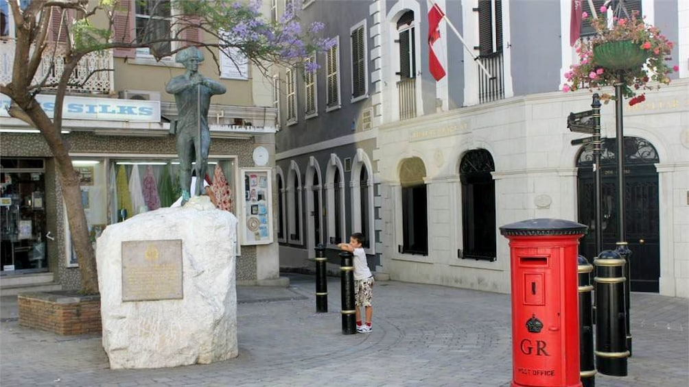 Show item 4 of 10. Statue and shops in Gibraltar