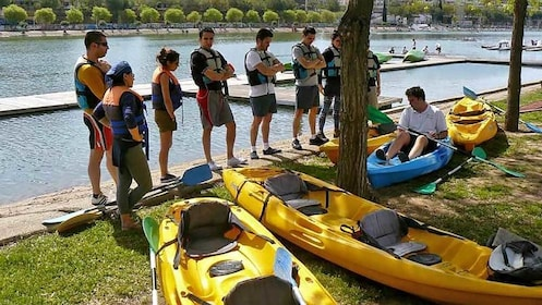 group sorting out kayaks along the water in Spain