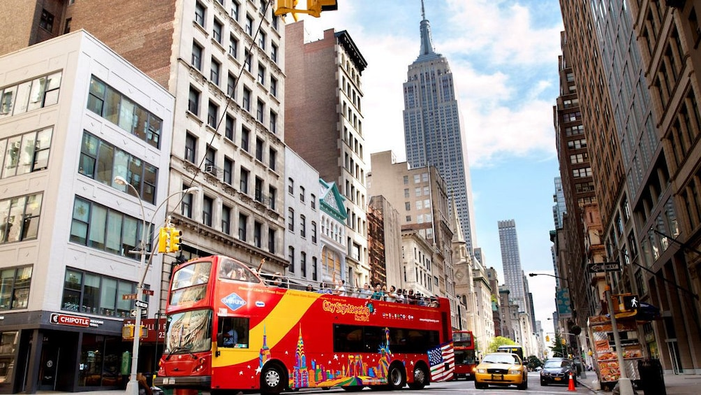 Show item 5 of 10. Double decker bus drives within the view of the Empire State Building