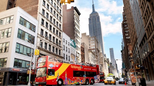 Double decker bus drives within the view of the Empire State Building