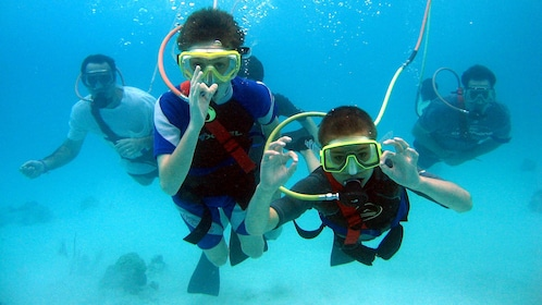 Two men and two boys doing the 'OK' sign SNUBA dive in Bermuda