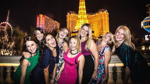 Group of women posing in front of strip.