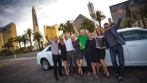 Group posing in front of limo in the evening.