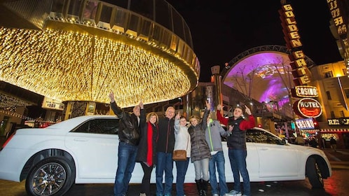 Group posing in front of limo at night.