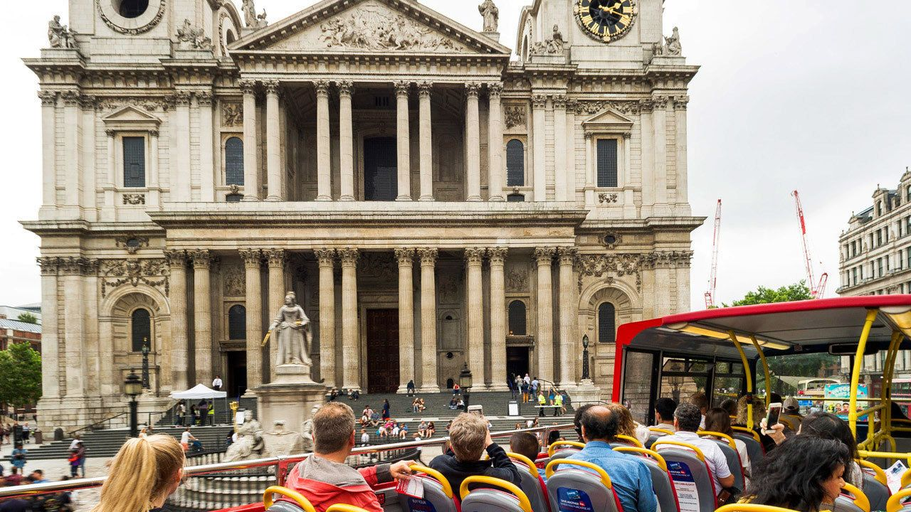 People on double decker tour bus viewing historical building in London