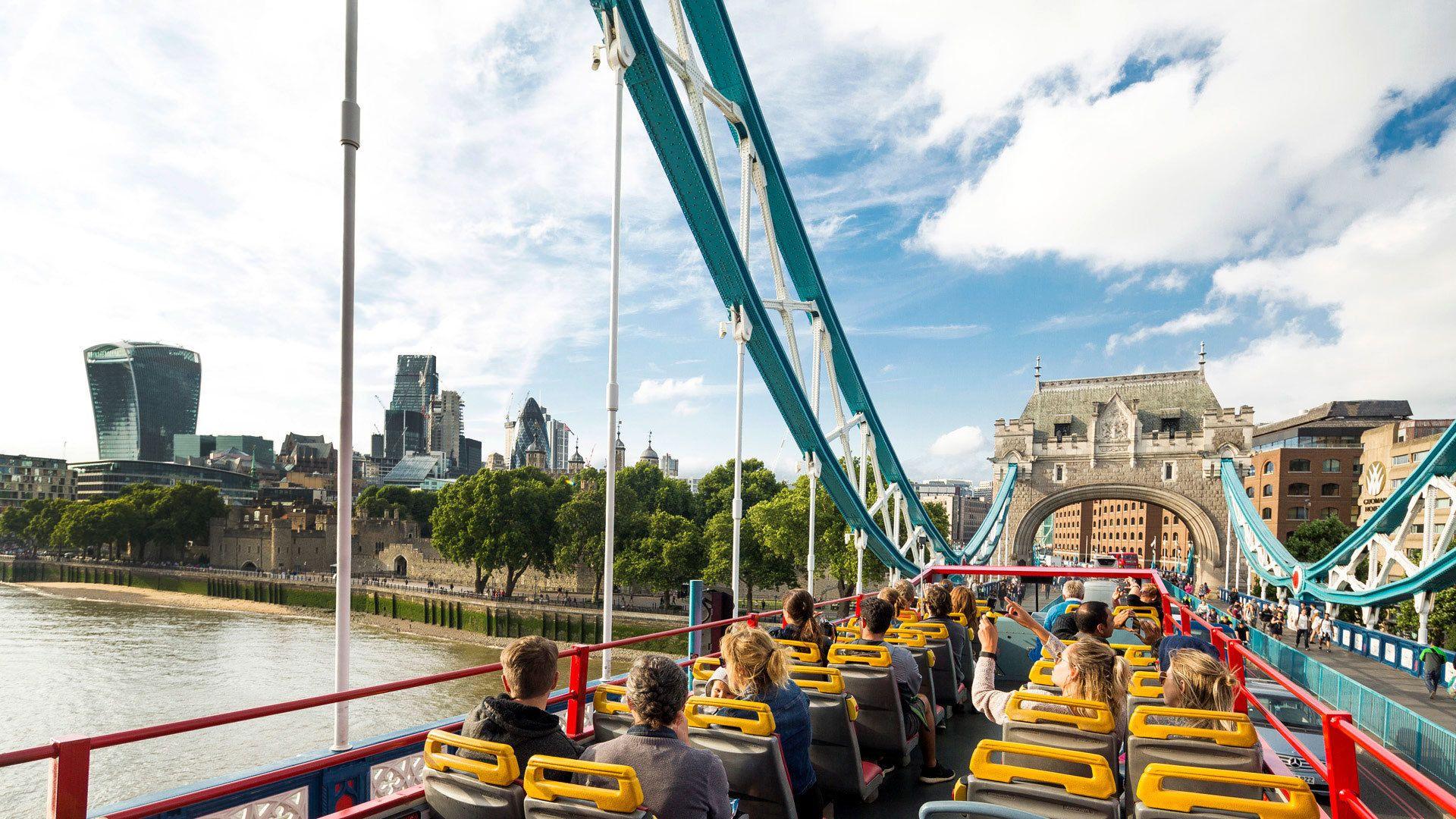 People on double decker tour bus traveling across bridge in London