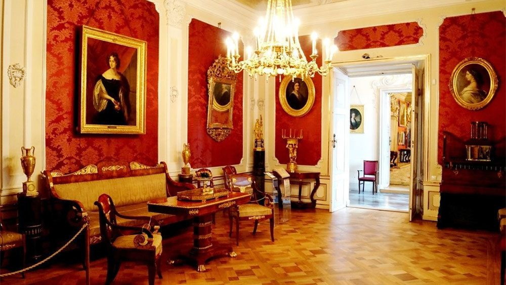 Red-walled interior with portraits and a chandelier inside Wilanow Palace in Warsaw