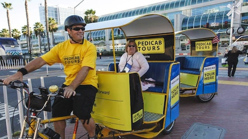Woman on pedicab with driver in front.