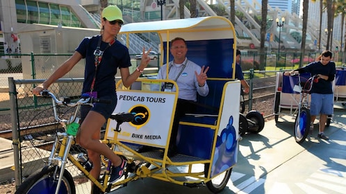 Man in a pedicab with driver in San Diego