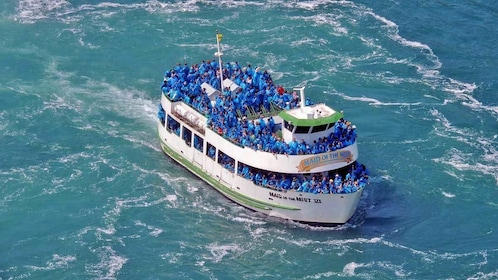 boat passengers in blue ponchos nearing the waterfall in Niagara Falls