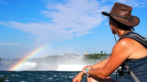 woman looking at a rainbow by the waterfall at Niagara Falls