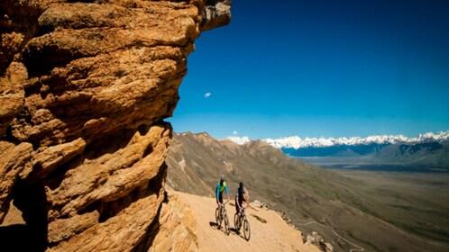 Cyclists riding across mountain area.