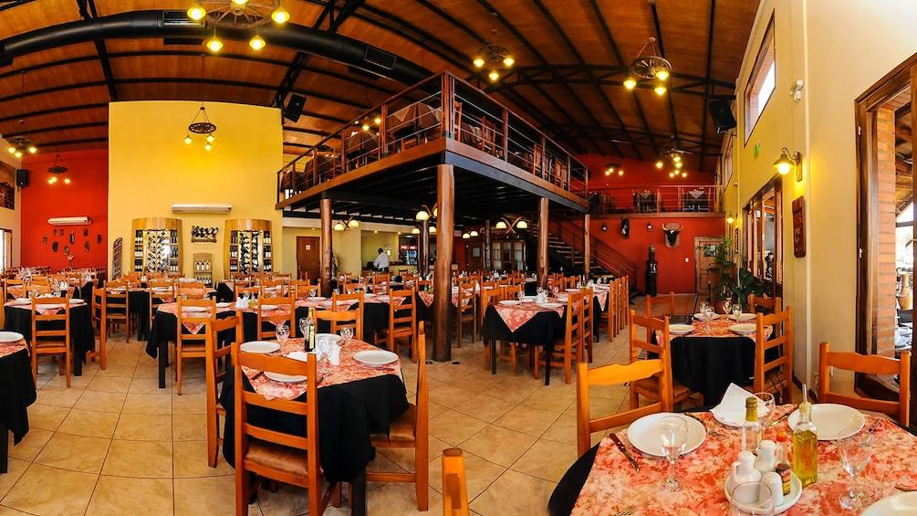Foto 4 von 10 laden Interior view of empty restaurant with prepared dinner tables.