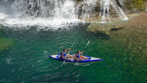 Two kayakers pass a waterfall