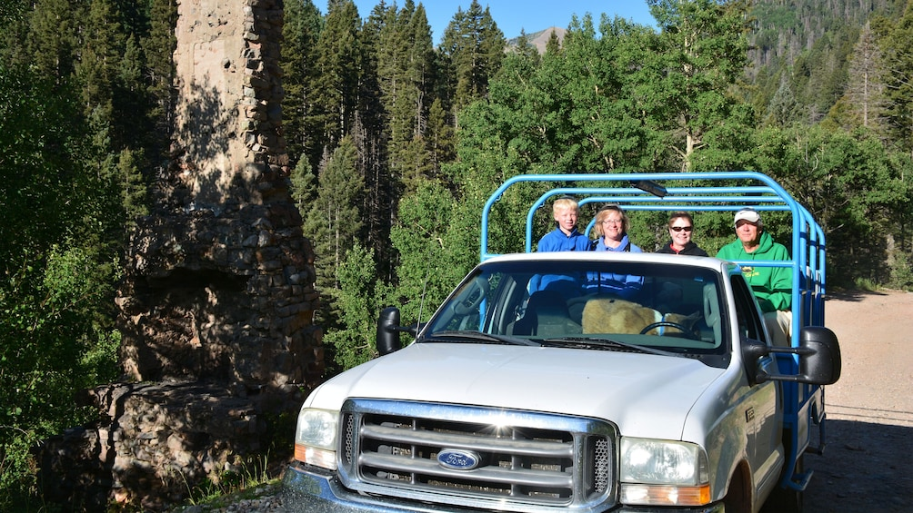 Show item 3 of 9. Tourist on tour truck on dirt road in the mountains outside of Denver