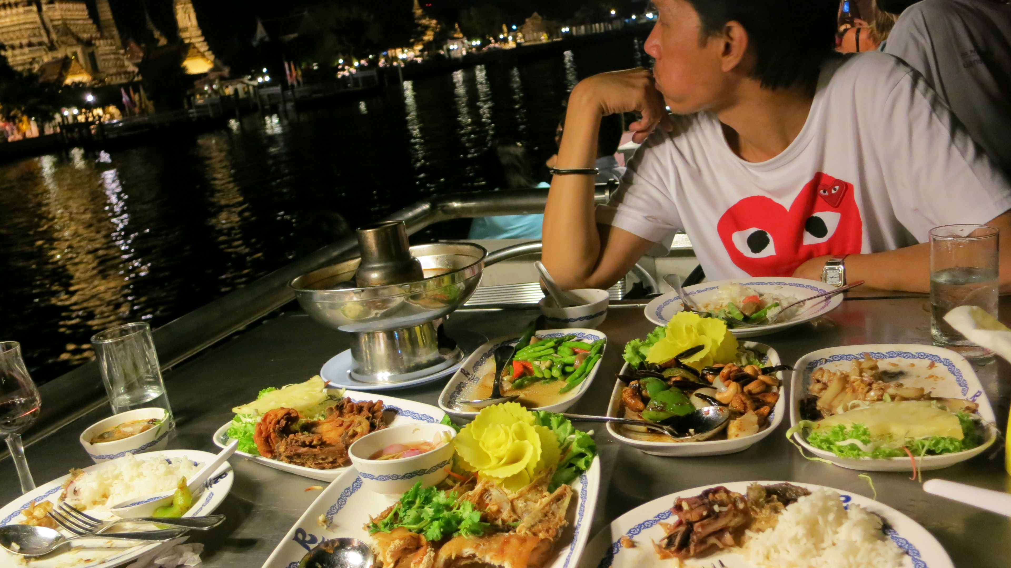 Man seated at dinner table with several dishes observing skyline.