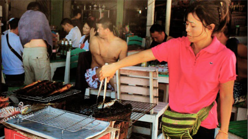 Show item 3 of 5. Woman grilling fish at a restaurant on Coral Island