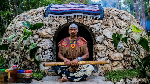 Shaman sitting in front of a rock hut in Cancun