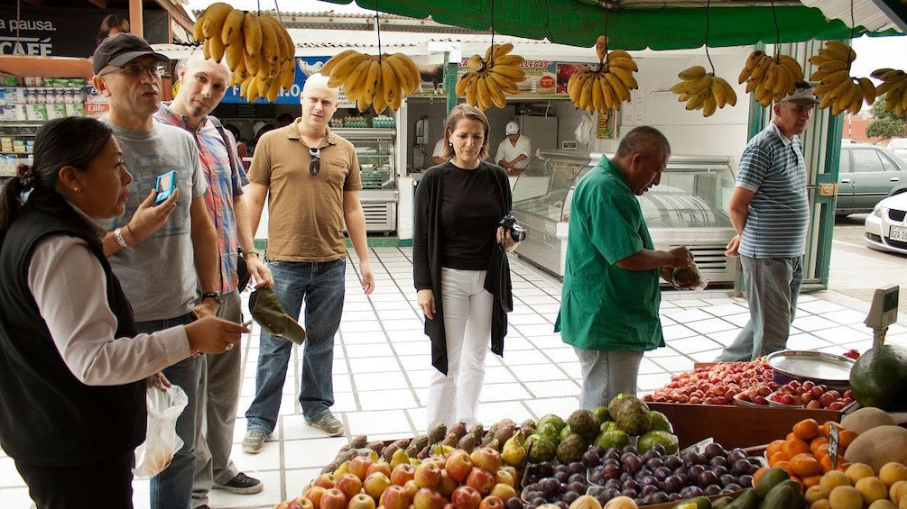 Show item 1 of 8. Tour group at a produce market in Lima