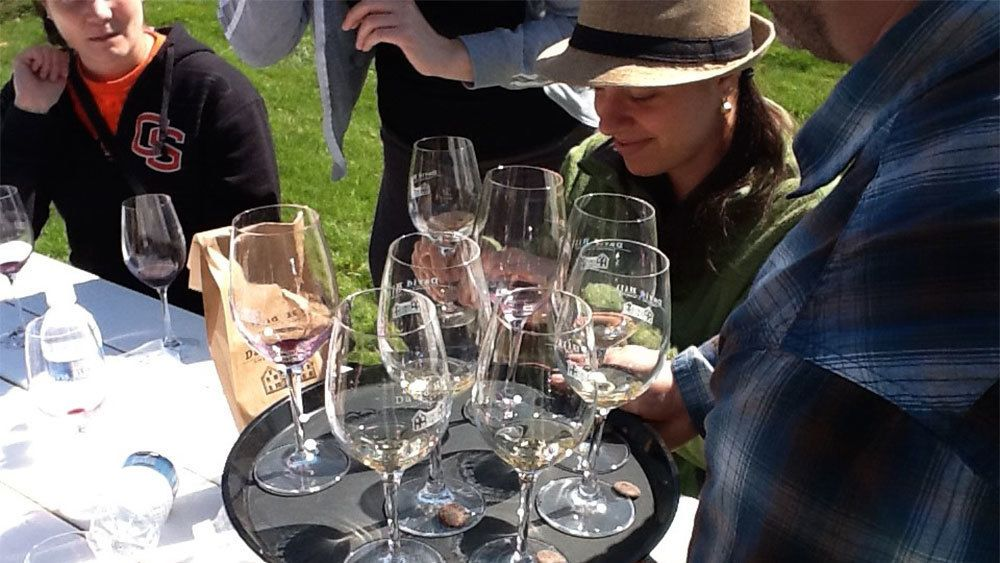 Group with a tray of wine glasses outside a winery in Portland