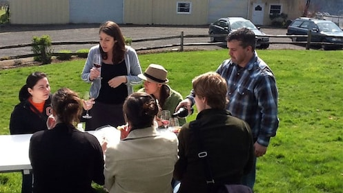 Sommelier pouring wine for a group outside at a winery in Portland