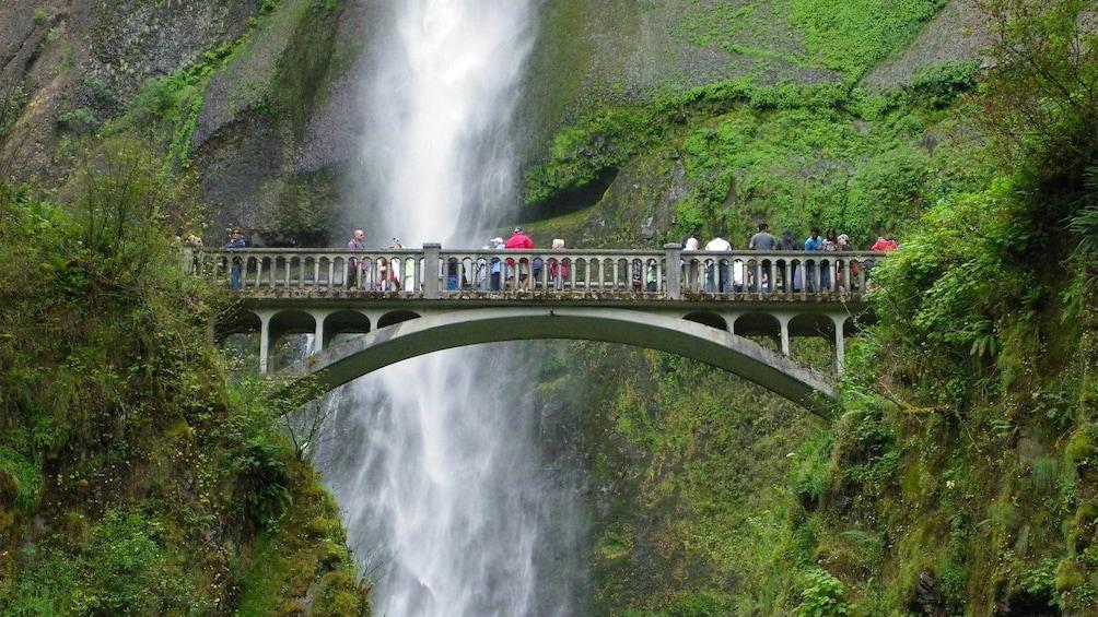 Tourists on the bridge overlooking the Multnomah Falls in Portland