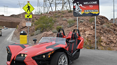 Angled view of red and black Slingshot vehicle parked by Welcome to Nevada sign.