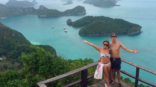 Two people pose in view of Thai islands