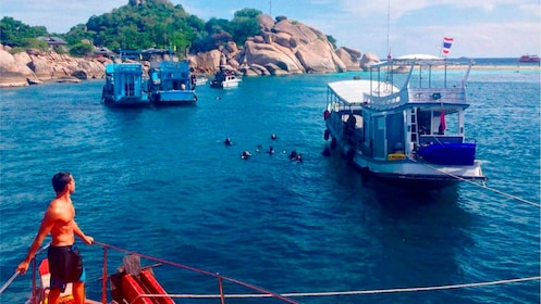 Snorkelers at a Thailand bay next to boats