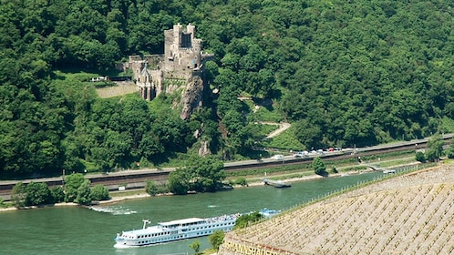Boat on the Rhine River passing a medieval castle and surrounding forest