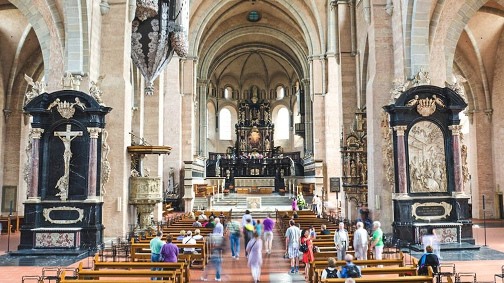 Show item 1 of 5. Interior view of cathedral with several people inside.
