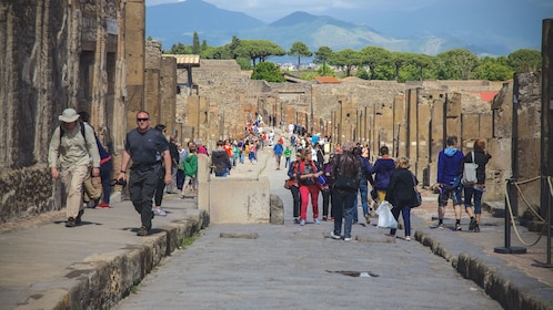 Tourists navigating around Pompeii ruins.