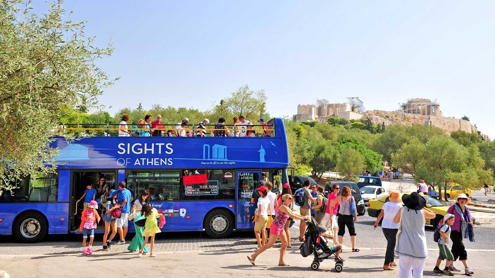 blue double deck bus at a busy intersection in Athens