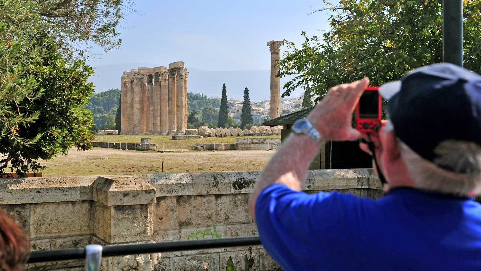 man taking photos of old standing columns in Athens
