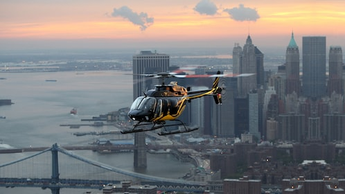 A Helicopter flying above the New York skyline at dusk