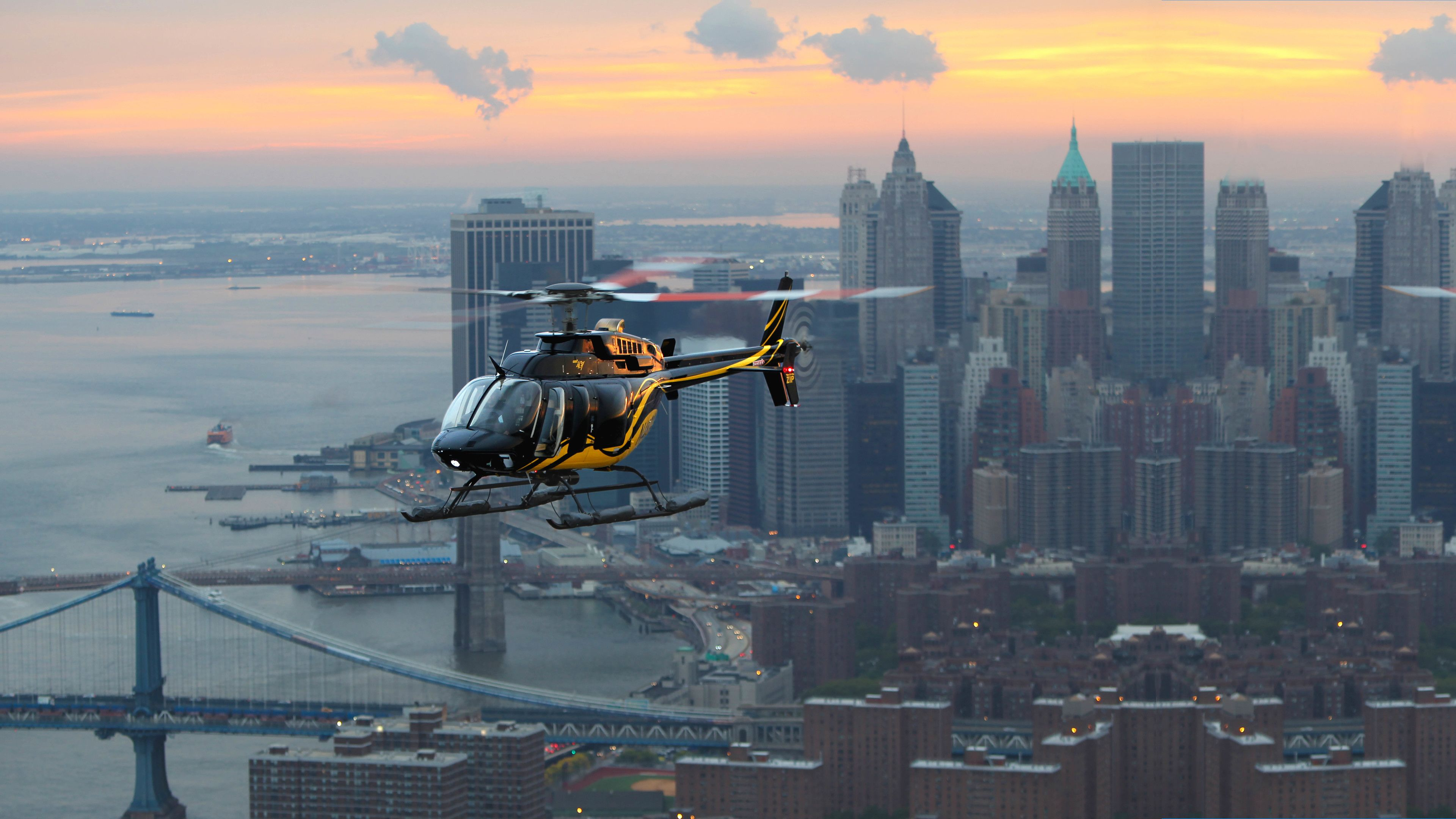 Helicopter flying over city at sunset.